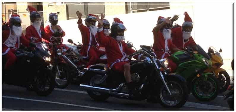 Biking Santas in Brisbane, Queensland, cheerfully waving and honking - Henny Jensen